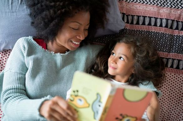 Overhead-view-smiling-mother-and-daughter-reading-book-on-bed